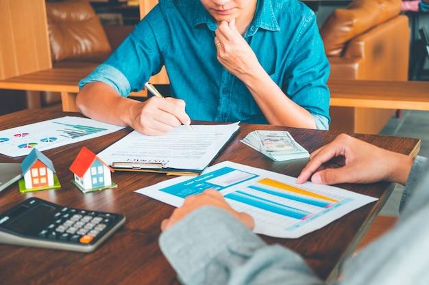 Contrat de maison, man signe un contrat pour acheter une maison avec un agent immobilier