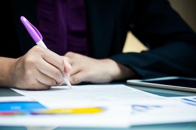 Contrat de signature de contrat de close-up businessperson avec document de données graphique sur le bureau