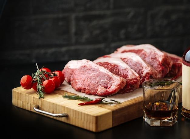 Contre-filet de steak cru cru new york sur une planche de bois avec tomates et romarin