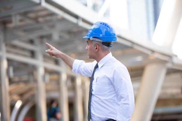 Contremaître avec contrôle du casque sur le chantier.