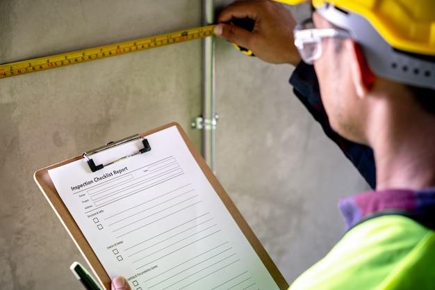 Contremaître avec des documents mesurant un mur