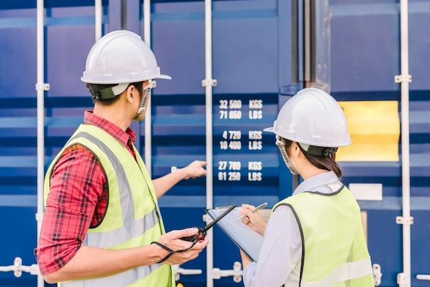 Contremaître et personnel vérifiant la boîte de conteneur