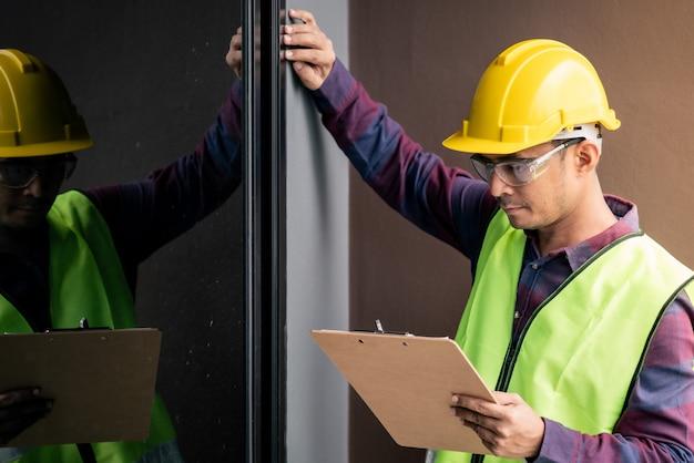 Contremaître avec presse-papiers inspectant une maison