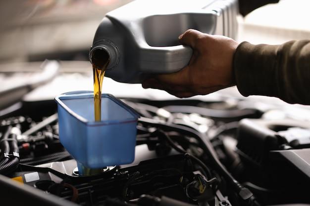 Le contremaître verse de l'huile de voiture dans le moteur à l'aide d'un arrosoir. concept d'intervalles de vidange d'huile moteur