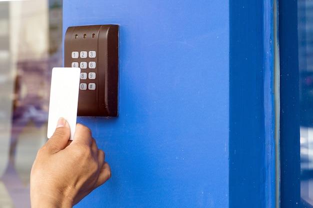 Contrôle d'accès à la porte - jeune femme tenant une carte-clé pour verrouiller et déverrouiller la porte.
