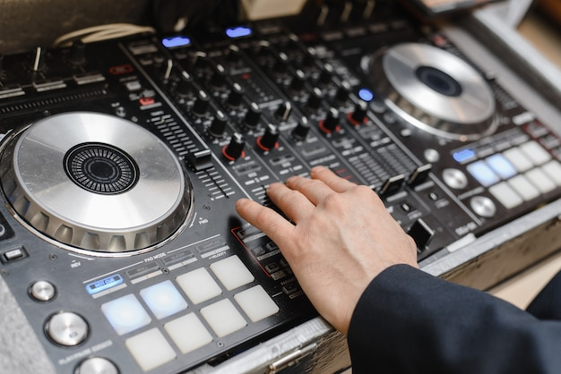 Contrôle dj. homme jouant dj set. les mains sur un disque