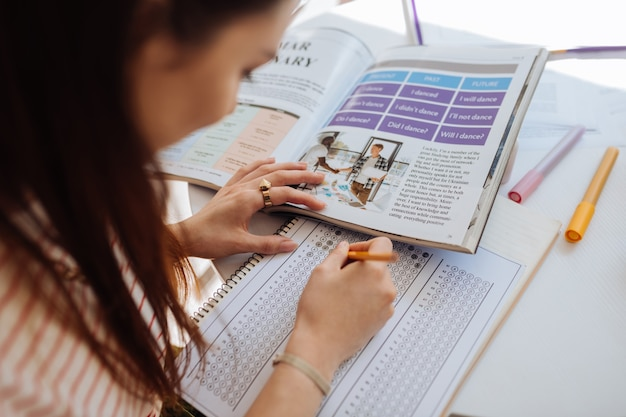 Contrôle d'essai. femme brune concentrée inclinant la tête tout en prenant des notes