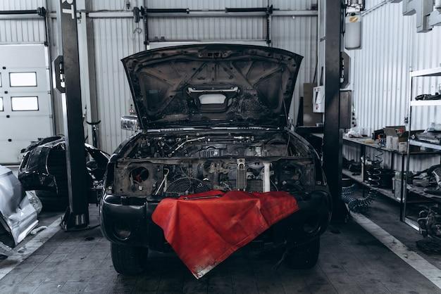 Contrôle saisonnier de la voiture. voiture noire avec coffre ouvert debout au garage au service. stock photo