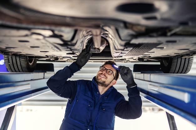 Contrôle technique de la voiture. service de voiture dans l'atelier. un homme en uniforme bleu se tient sous une voiture dans le garage et vérifie les essieux des voitures. il illumine le châssis avec une lampe de poche