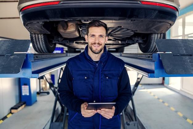 Contrôle technique des voitures et des tablettes. un homme en uniforme tient une tablette dans ses mains dans le canal de l'atelier devant une voiture sur un ascenseur hydraulique portrait d'un homme au travail dans un atelier service de voiture