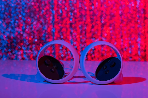 Contrôleurs de réalité virtuelle pour les jeux en ligne et en nuage sur fond blanc à la lumière du néon. vr, avenir, gadgets, concept technologique.