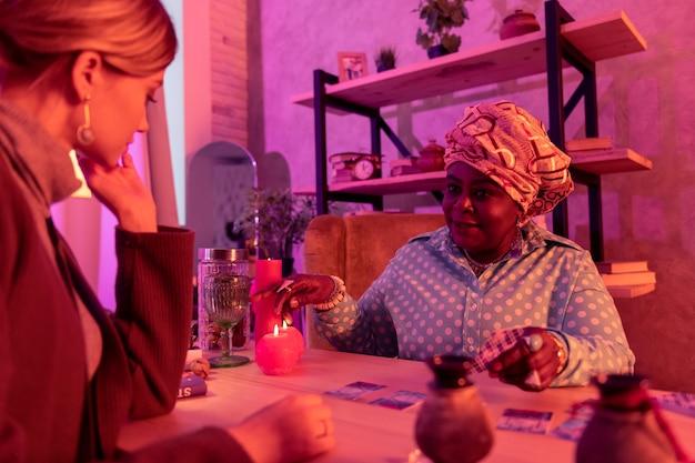 Conversation. african american dodue diseuse de bonne aventure portant une énorme bague pointant vers une tasse tout en expliquant la signification des cartes