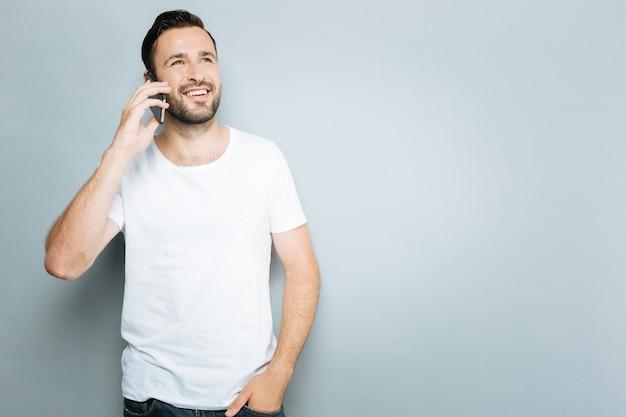 Conversation amicale. homme souriant tenant le téléphone près de l'oreille et mettant la main gauche dans la poche, debout sur fond gris