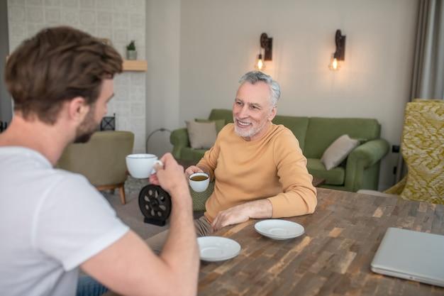 Conversation. deux hommes assis à table, prenant le thé et parlant