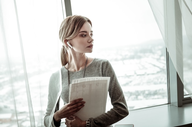 Conversation avec le partenaire. femme d'affaires élégante blonde portant des écouteurs tout en ayant une conversation avec son partenaire