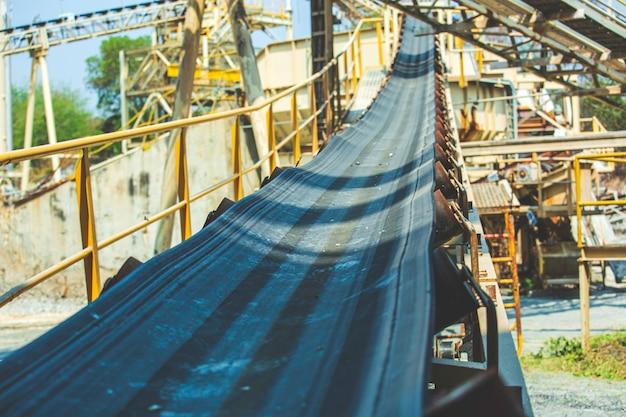Convoyeur à bande industriel déplaçant les matières premières de la mine d'or