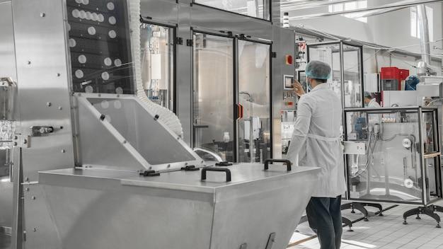 Convoyeur avec couvercles pour bouteilles à l'usine de lait. équipement à l'usine laitière