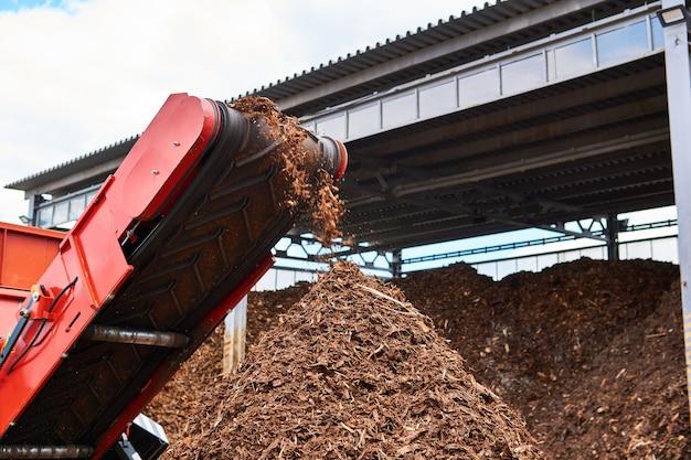 Convoyeur en gros plan d'un broyeur de bois industriel produisant des copeaux de bois à partir d'écorce