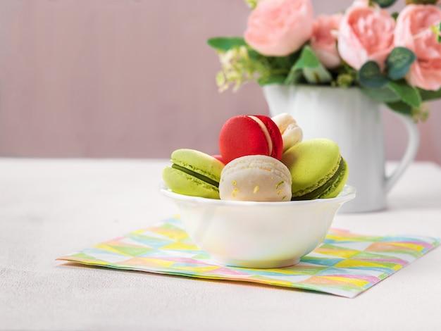 Coockie français macaron ou macaron sur fond clair avec des fleurs de printemps, couleurs pastel.
