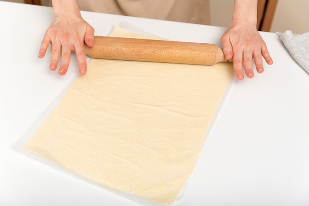 Cook étale la pâte finement avec un rouleau à pâtisserie