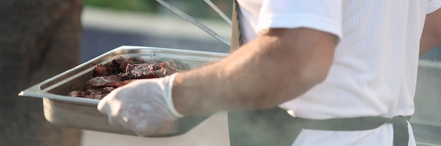 Cook porte une plaque à pâtisserie avec de la viande grillée