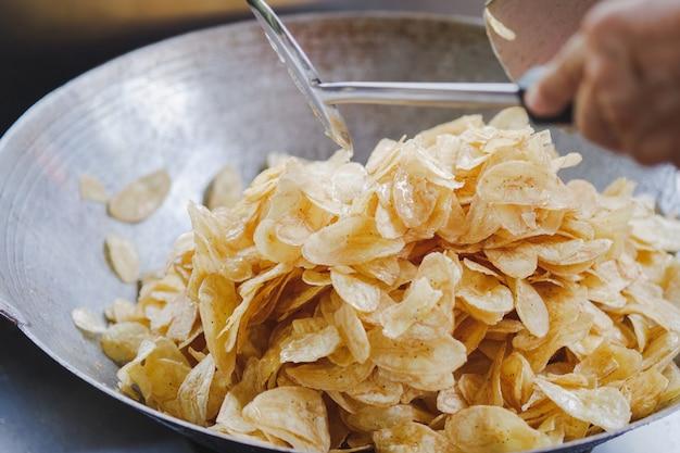 Cook prépare des chips de banane sucrées en faisant frire des bananes dans la poêle.