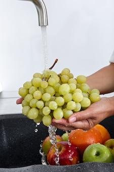 Cook woman lave une grappe de raisin sous l'eau qui coule d'un robinet.