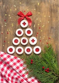 Cookie de linzer disposé sous la forme d'un arbre, décoré d'un tissu, de brindilles et d'étoiles.