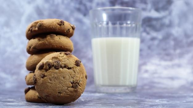Cookies américains aux pépites de chocolat empilés les uns sur les autres avec du lait dans un verre sur fond gris. pâte croustillante arrondie traditionnelle aux pépites de chocolat. boulangerie. dessert délicieux, pâtisseries.