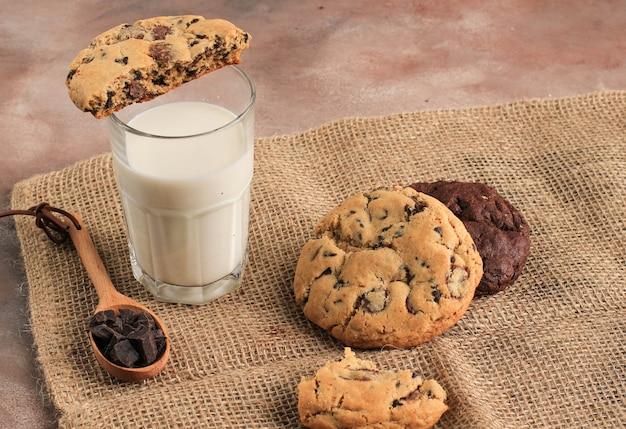 Cookies aux pépites de chocolat américain, biscuits moelleux servis avec un verre de lait frais sur fond marron. copiez l'espace pour le texte ou la recette