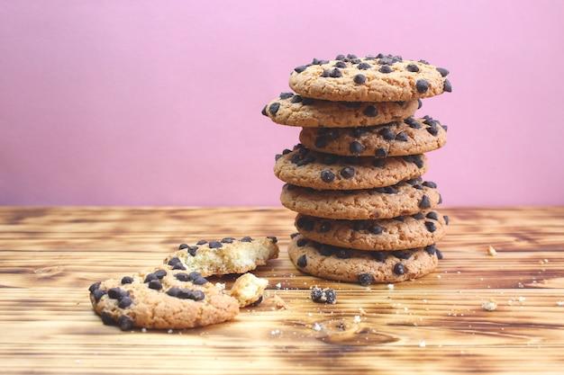 Les cookies aux pépites de chocolat empilés les uns sur les autres dans une pile se dresse sur une table en bois. collation sucrée au petit-déjeuner.
