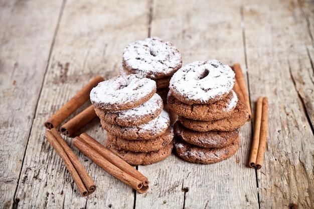Cookies aux pépites de chocolat frais cuits au four avec du sucre en poudre et des bâtons de cannelle sur une table en bois
