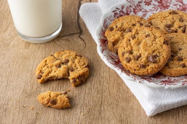 Cookies aux pépites de chocolat et à la vanille sur une assiette décorée sur textile avec cookie cassé et un verre de lait sur une table en bois.