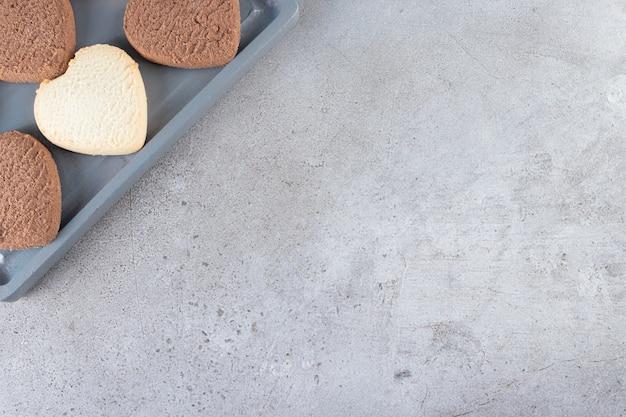 Cookies coeurs au chocolat placés sur une table en pierre.