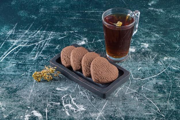 Cookies coeurs au chocolat avec une tasse de thé noir placé sur une table en pierre.