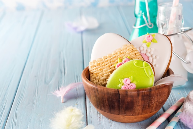 Cookies colorés de lapin de pâques dans un bol en bambou sur un fond en bois bleu