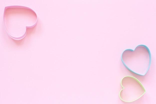Cookies de coupeurs colorés en forme de coeur sur fond rose pastel. carte de la saint-valentin.