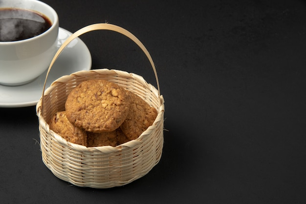 Cookies dans un panier en bambou et une tasse de café sur fond noir