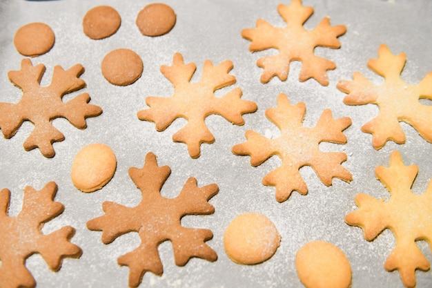 Cookies de flocon de neige. biscuits de pain d'épice en forme de flocon de neige empilés et attachés avec un arc en or.