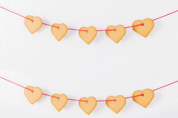 Cookies en forme de coeur accroché à un mur blanc. symbole d'amour chaleureux et fond de la saint-valentin et concept festif