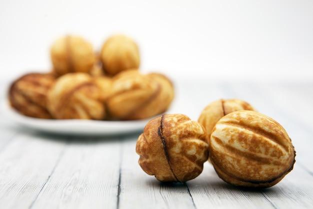 Cookies - noix sur une table en bois, à côté d'une assiette avec des pâtisseries floues