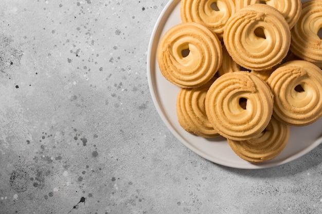 Cookies sur une plaque en céramique blanche sur la table de cuisine grise. vue de dessus avec espace copie