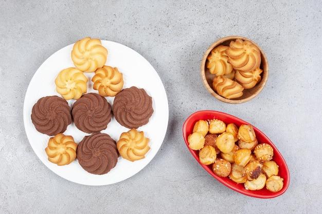 Cookies regroupés dans divers articles de table sur une surface en marbre.