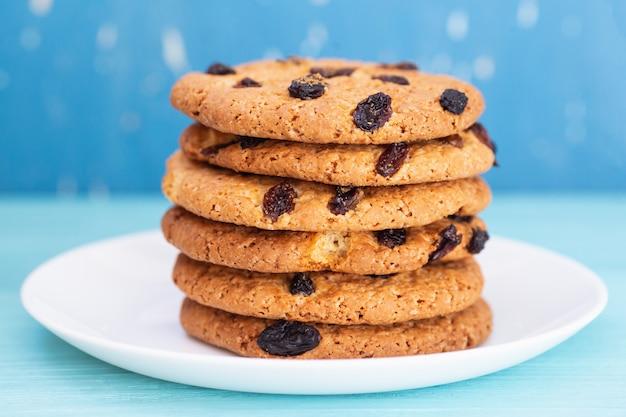 Cookies tasly aux raisins secs sur une plaque blanche. fond bleu