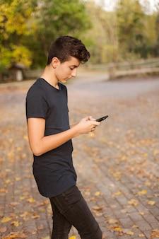 Cool adolescent avec un téléphone portable dans la rue