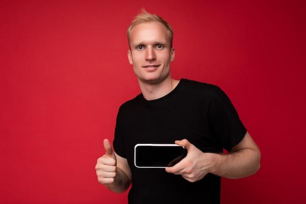 Cool beau jeune homme blond sérieux portant un tshirt noir debout isolé sur fond rouge avec