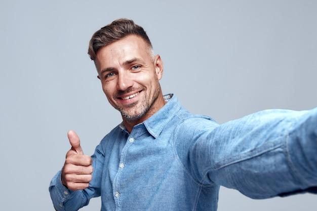 Cool cheerful barbu in shirt faisant selfie et montrant le pouce en se tenant debout sur fond gris. notion numérique. émotion positive. la photographie