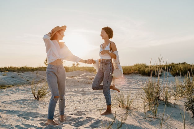 Cool deux jeunes femmes s'amusant sur la plage au coucher du soleil, romance d'amour lesbienne gay