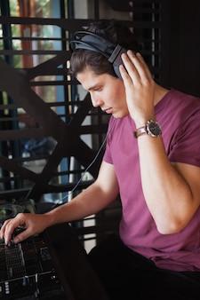 Cool dj travaillant sur un bureau de mixage sonore