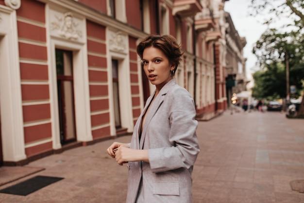 Cool femme en costume gris se penche sur la caméra à l'extérieur. portrait de jeune fille aux cheveux courts en veste surdimensionnée se promenant dans la ville
